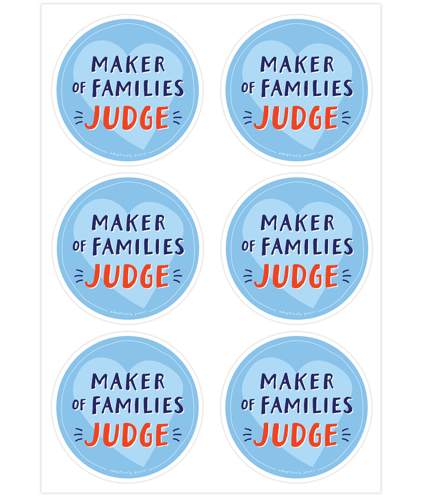 Set of six, 4 and 1/8 inch round durable matte vinyl weather resistant sticker. Easy to apply and reapply. 1/8 inch white border. Background is bright blue with light blue hand drawn heart. Hand illustrated words in dark blue read Maker of Families. Below is the word Judge in bright red with dark blue dashes on each side. In tiny casual font the words adoptionly yours tm are part of a thin white hand drawn border.