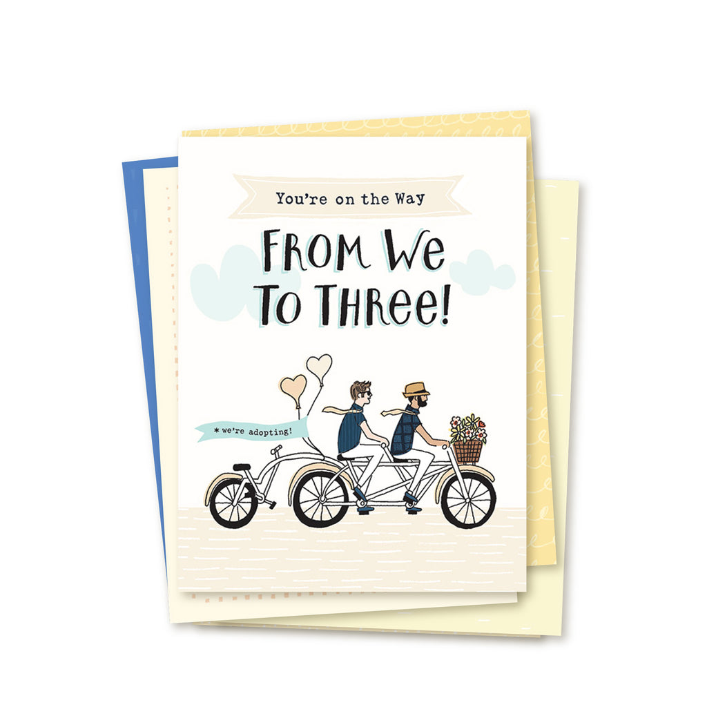 Image showing stack of adoption greeting cards in 6-card set for encouraging two adopting dads along the adoption journey. Top card image of two hopeful dads riding a two-person bicycle. Text reads: YOU'RE ON THE WAY FROM WE TO THREE! Set includes six, 4.25 x 5.5 inch greeting cards and envelopes. Blank inside.