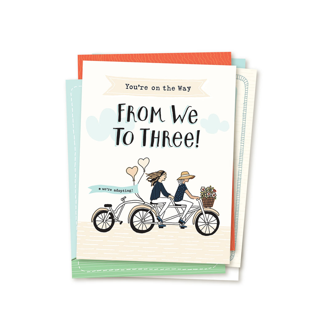 4.25 x 5.5 inch greeting card. Blank inside. Simple and charming illustration style. Title You're on the Way From We to Three! Main image is two women on a tandem bicycle. The woman in front is wearing large brim hat and the woman in back is wearing a head band and has long hair. The third wheel of the bike has a back seat and it is empty. There are flowers in the basket and balloons on the back of the bike with the words we're adopting!