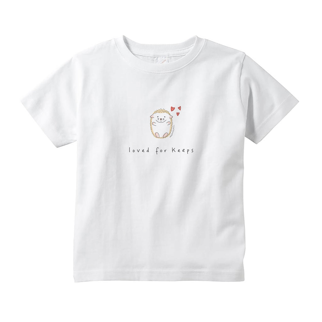 White 100% combed ringspun cotton toddler tee with tear-away label and topstitched rib collar. Small graphic in the center of the tee of simple and charming hand drawn hedgehog sitting with arms outstretched with three small red hearts above head. Below the hedgehog are hand drawn words in black that read loved for keeps.