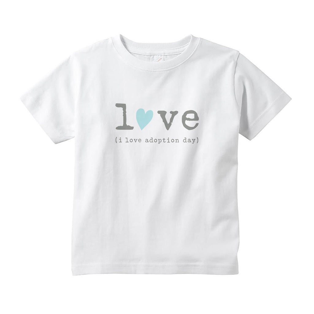"White 100% combed ringspun cotton toddler tee with tear-away label and topstitched rib collar. Graphic is in center of tee shirt in gray lowercase typewriter font spelling out the word love. The ""o"" in love is replaced with a hand drawn light teal blue heart tilted to the right. Below the word love is gray typewriter font and reads (i love adoption day)."