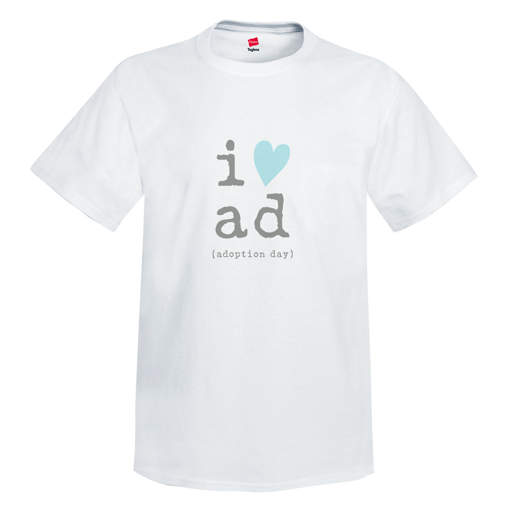 White 100% cotton pre-shrunk tee. Crewneck unisex tee with and tag-less label. Graphic is in center of onesie in gray lowercase typewriter font with the letter i and a blue heart graphic. Stacked underneath are the letters a and d in gray typewriter font. Below a and d are the words in gray typewriter font and reads (adoption day).