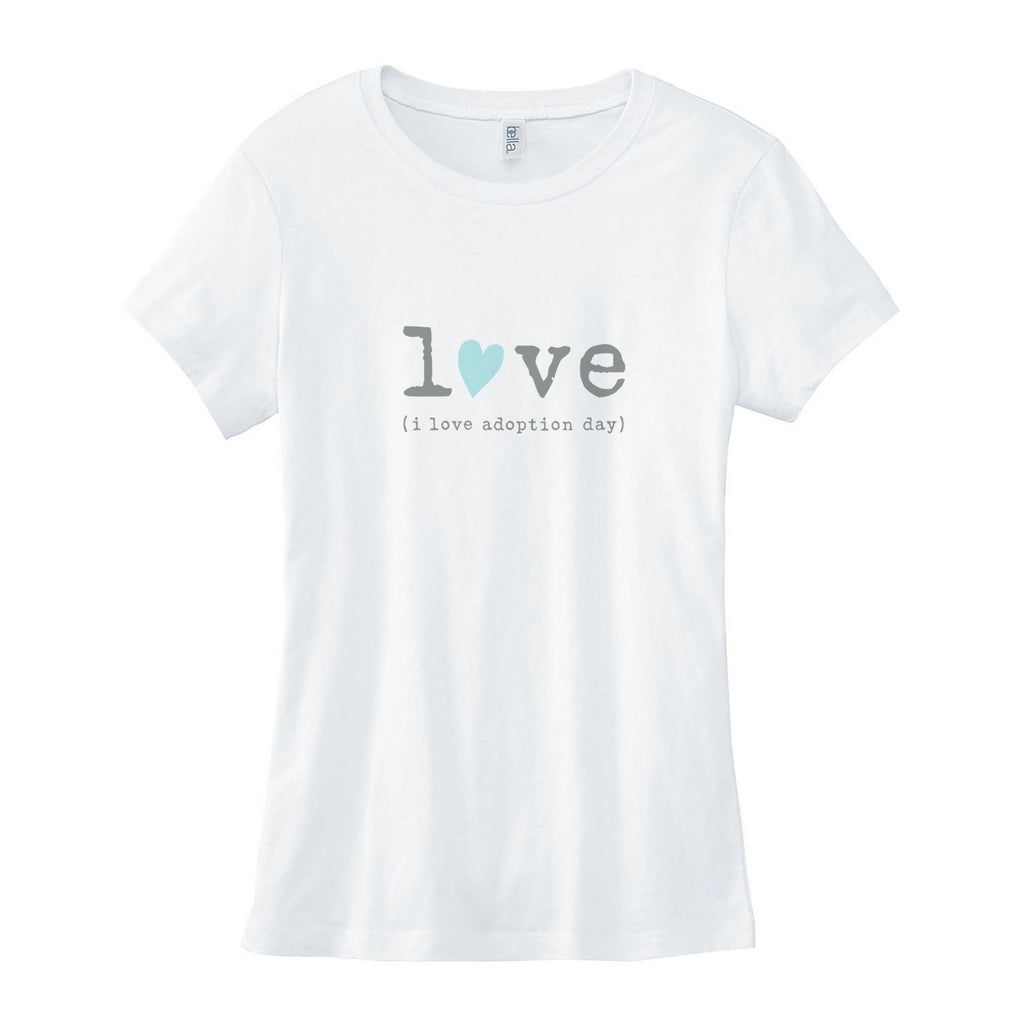 "White 100% combed ringspun cotton slim fit crewneck tee. Longer length with cap sleeves. Graphic is in center of tee shirt in gray lowercase typewriter font spelling out the word love. The ""o"" in love is replaced with a hand drawn light teal blue heart tilted to the right. Below the word love is gray typewriter font and reads (i love adoption day)."