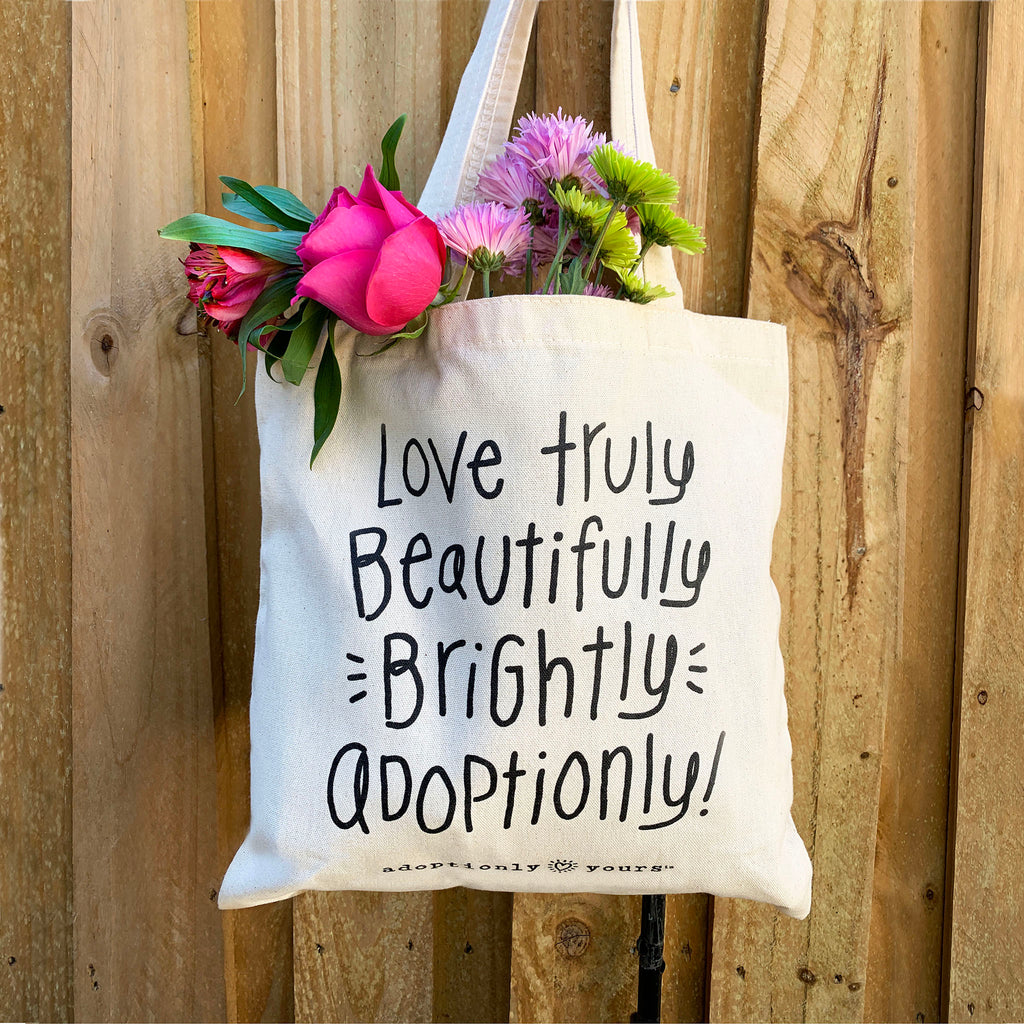 Photo of adoptionly yours natural cotton canvas tote filled with brightly colored flowers. Tote reads: love truly, beautifully, brightly, adoptionly.