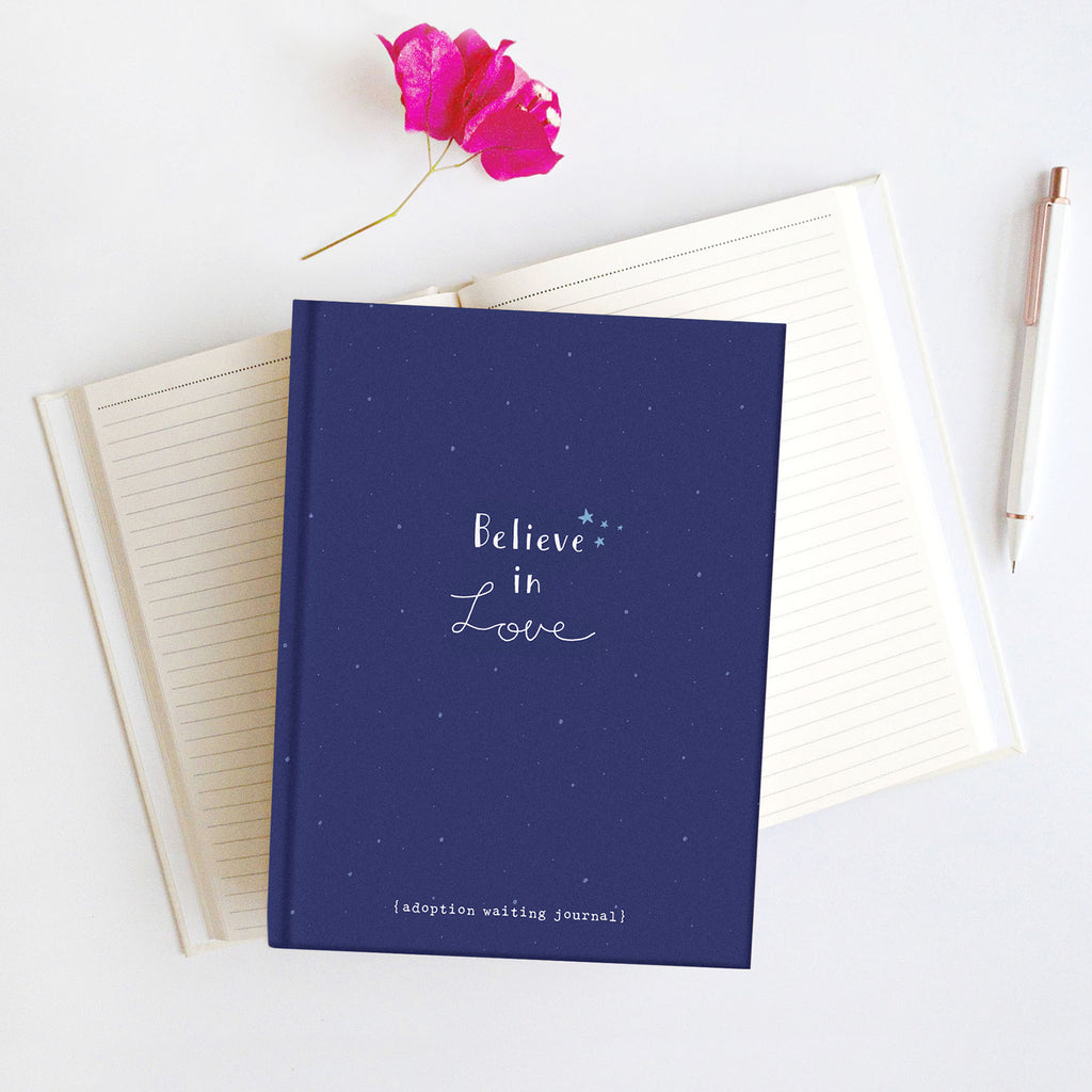 Photo of a Believe in Love Journal sitting on top of an open lined journal. Journal is deep blue with starry sky background. Says Believe in Love. Adoption Waiting Journal.