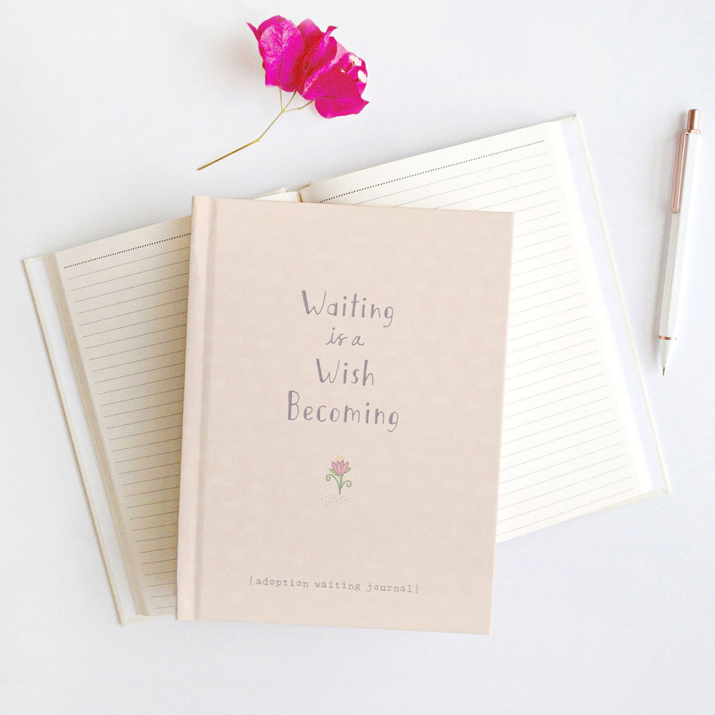 Product photo of Waiting is a Wish Becoming adoption waiting journal on top of open journal showing lined pages. Hard cover in soft peach color with an illustrated flower.