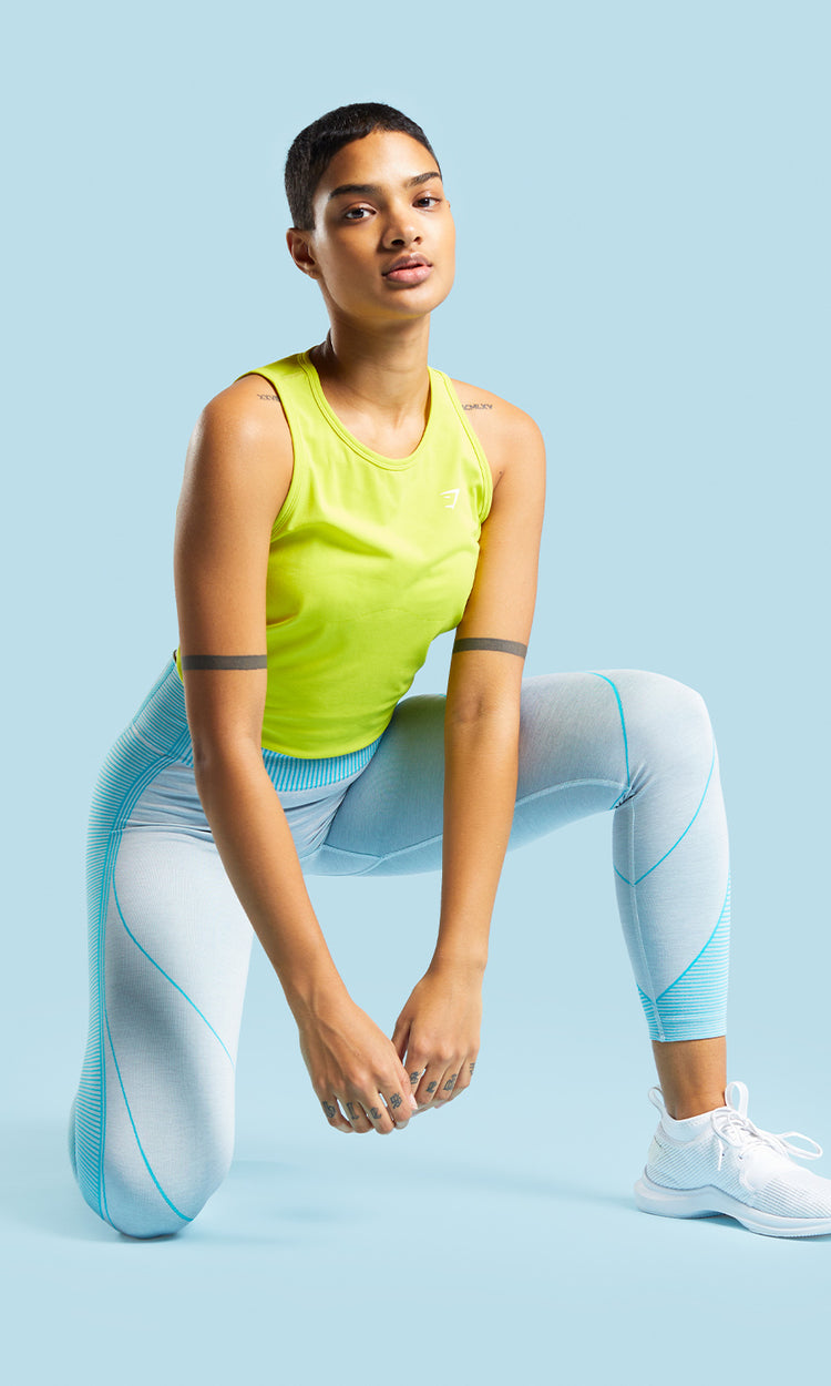 Model posiert in der Must-Have Hyper Amplify Kollektion mit den hellblauen Leggings und dem Tank in Lime.