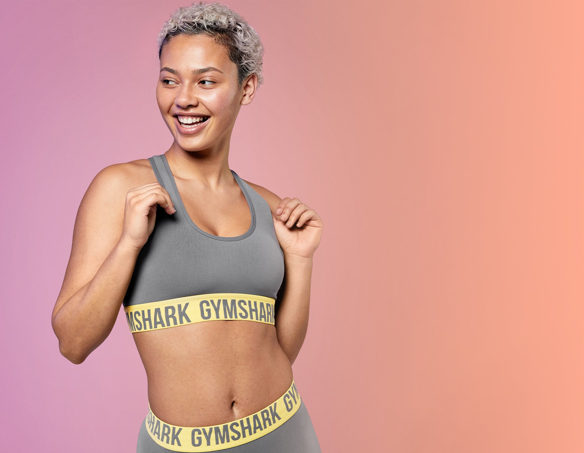 Weibliches Model trägt Fit Seamless Sports Bra und Shorts in Charcoal/Yellow.