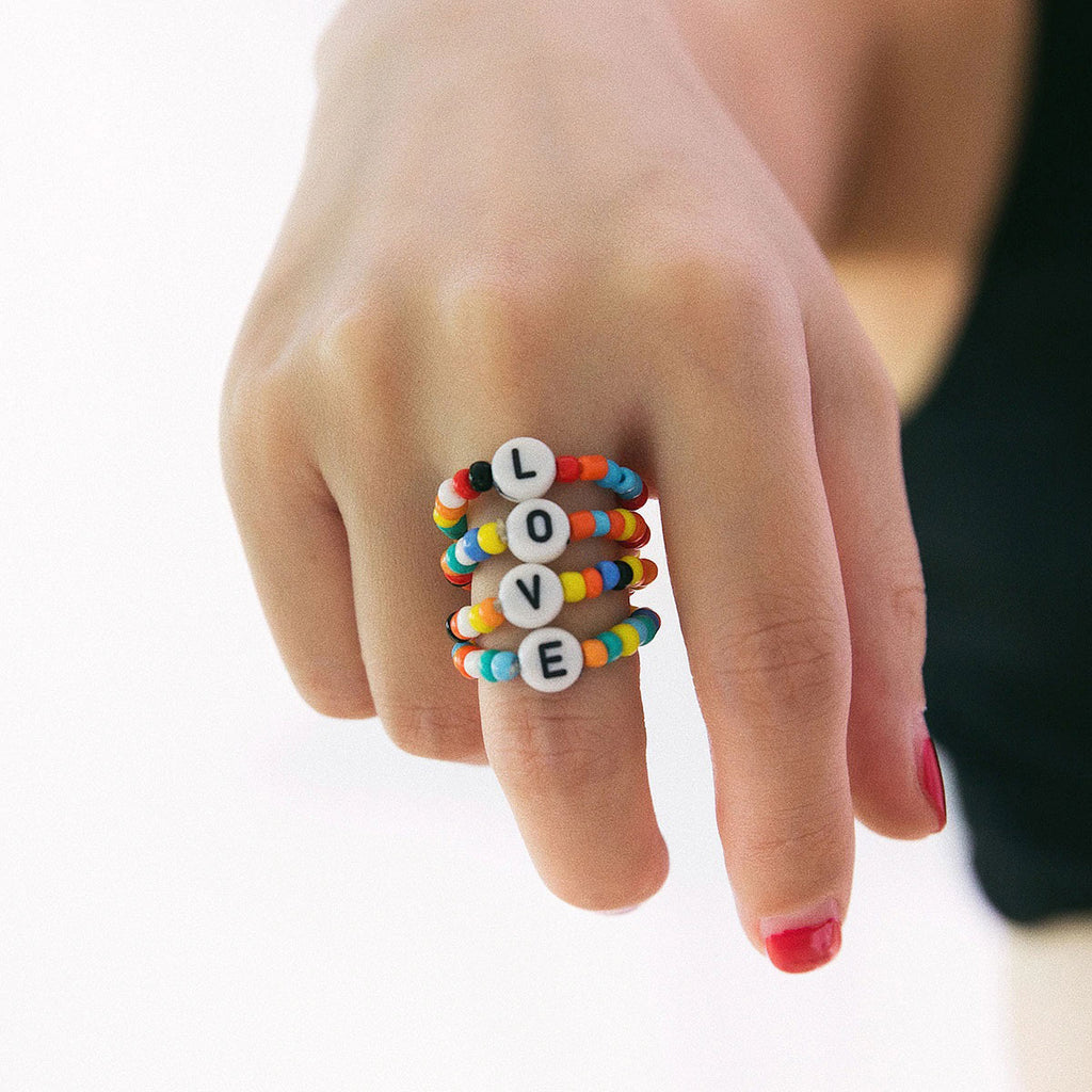 Woman Wearing Colorful Beaded Love Ring on Finger