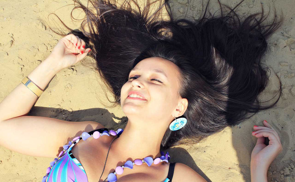 Smiling woman lying on beach and wearing jewelry
