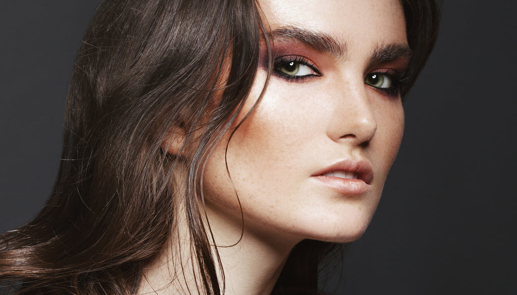 Close face shot of freckled brunette woman with green eyes wearing nude lips and creamy orange-toned eyeshadow Get the look Creamy Lids Sweet Sparkle