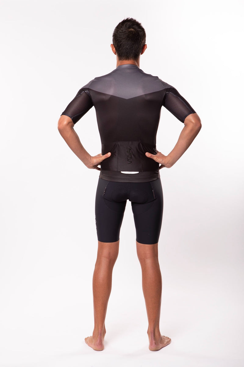 Back view model wearing men's Luceo Premium Cycling Jersey. Fast black and grey cycling jersey.