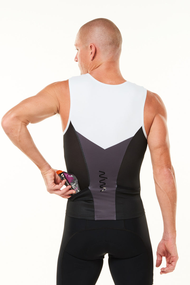 Model placing nutrition gel in back pocket of sleeveless tri top. Men's triathlon top with pockets.