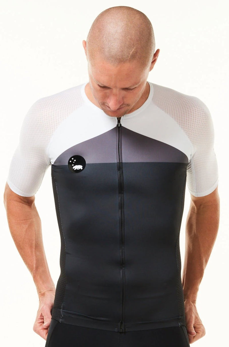 Model wearing WYN republic men's Tri Classics Aero+ Sleeved Top. Black, grey, white aero tri top.