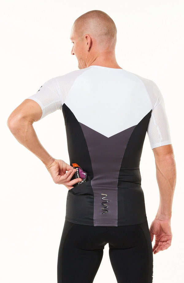 Model placing nutrition gel in back pocket of sleeved triathlon top. Men's tri top with pockets.