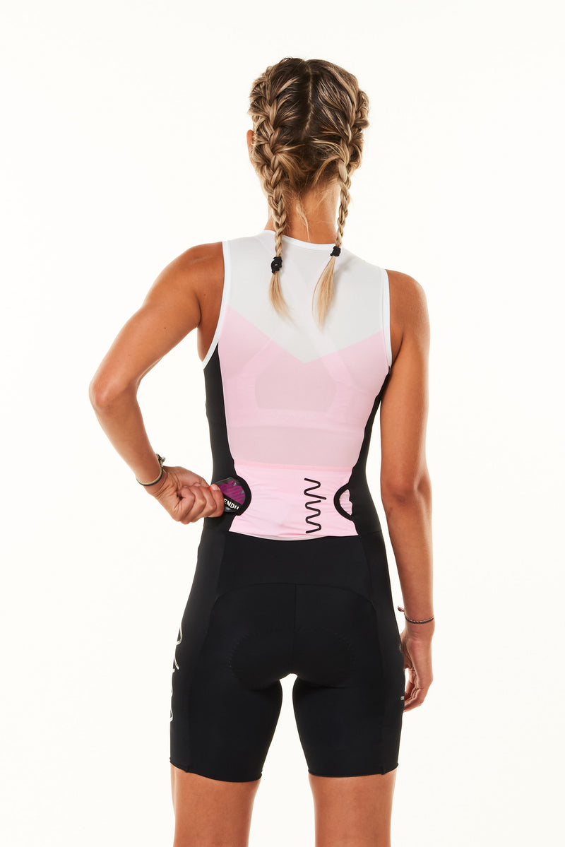Model placing nutrition gel in a back pocket of sleeveless tri suit. Women's triathlon suit with storage.