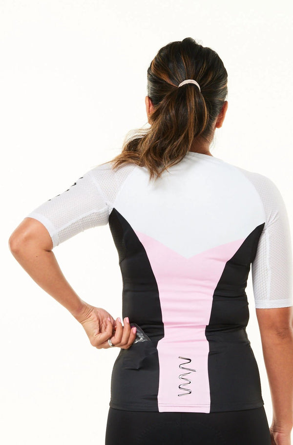 Model placing nutrition gel in back pocket of sleeved triathlon top. Women's tri top with pockets.