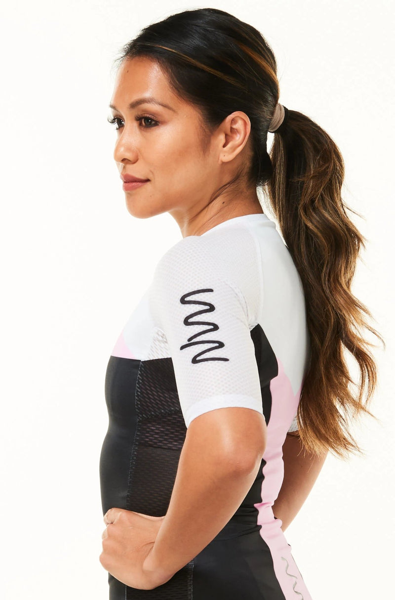 Showing left side women's Tri Classics Aero+ Sleeved Top. White Sleeve with black WYN republic logo.