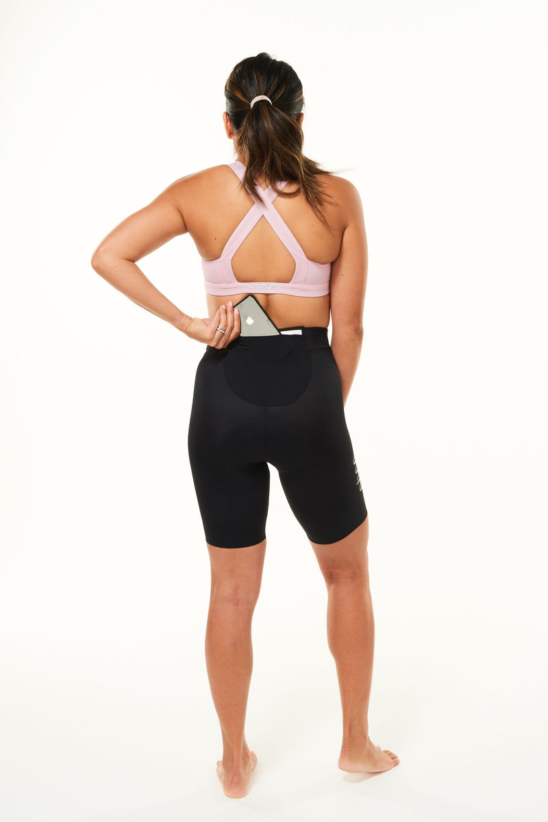 Model placing a phone in the back pocket of women's black tri shorts. Triathlon shorts with storage.