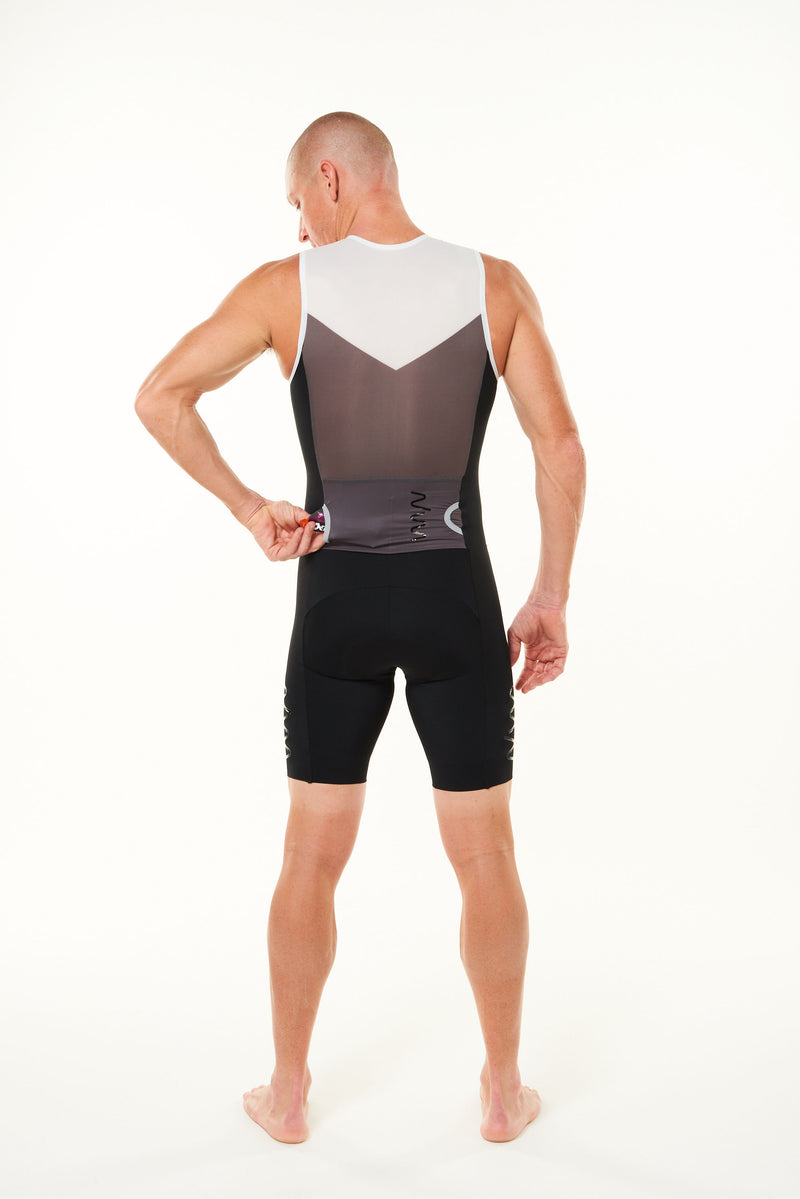 Model placing nutrition gel in back pocket of sleeveless tri suit. Men's triathlon suit with pockets.