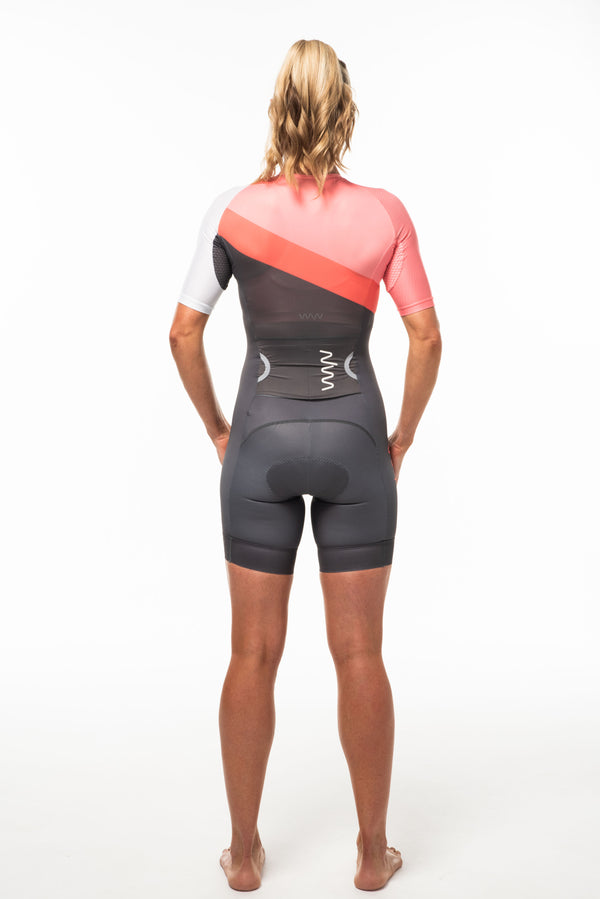 Back view model wearing Capri sleeved tri suit. Triathlon suit with large side entry back pocket.