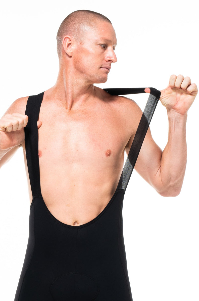 Model wearing men's black Velocity 2.0 Cycling Bib Shorts. Cycling shorts with stretch straps for comfort.