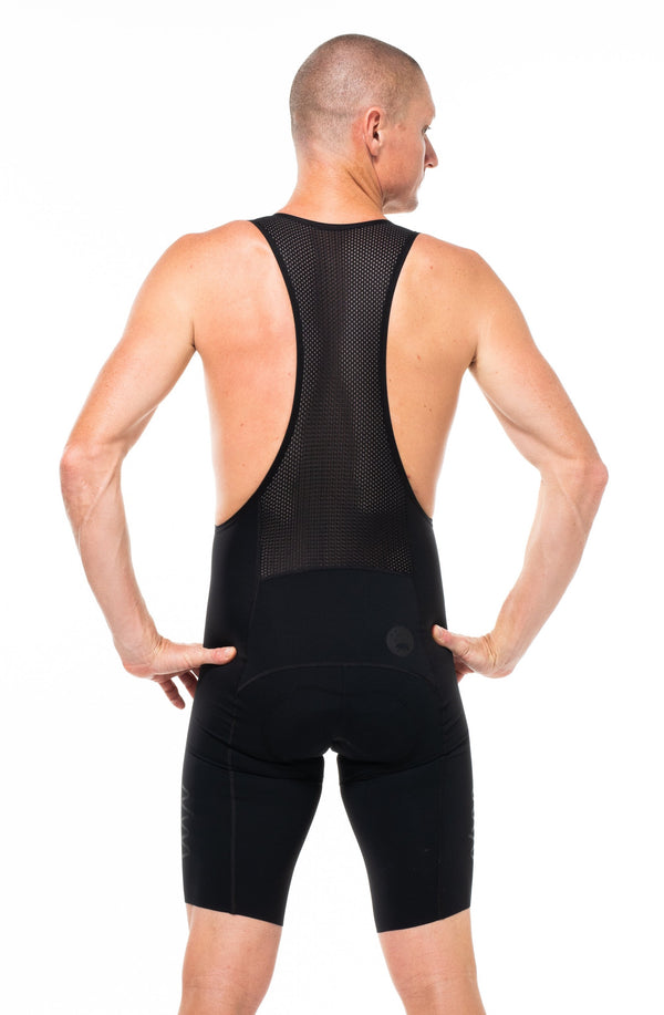 Back view of men's Velocity 2.0 Cycling Bib Shorts. Aerodynamic black cycling shorts with mesh back panel.