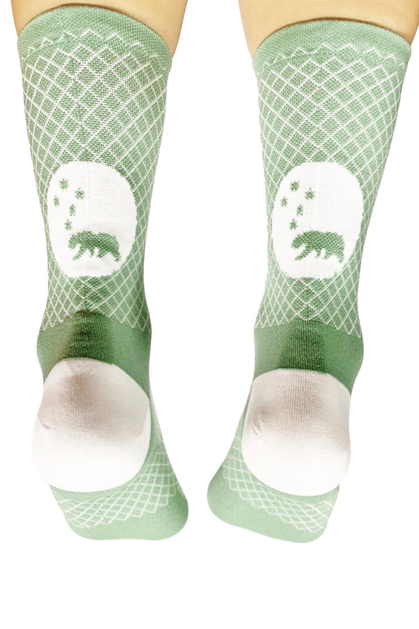 Back view of WYN republic Janis Socks. Green running/cycling socks with white argyle print and logo.