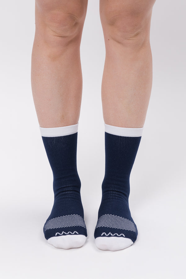 Front view women's Navy Captain Socks. Running & cycling socks with white logo and  dotted mid-foot.