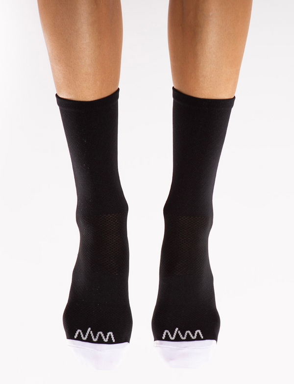 Front view Flagship socks. Mid-calf black cycling/running socks with white toe box and logo.