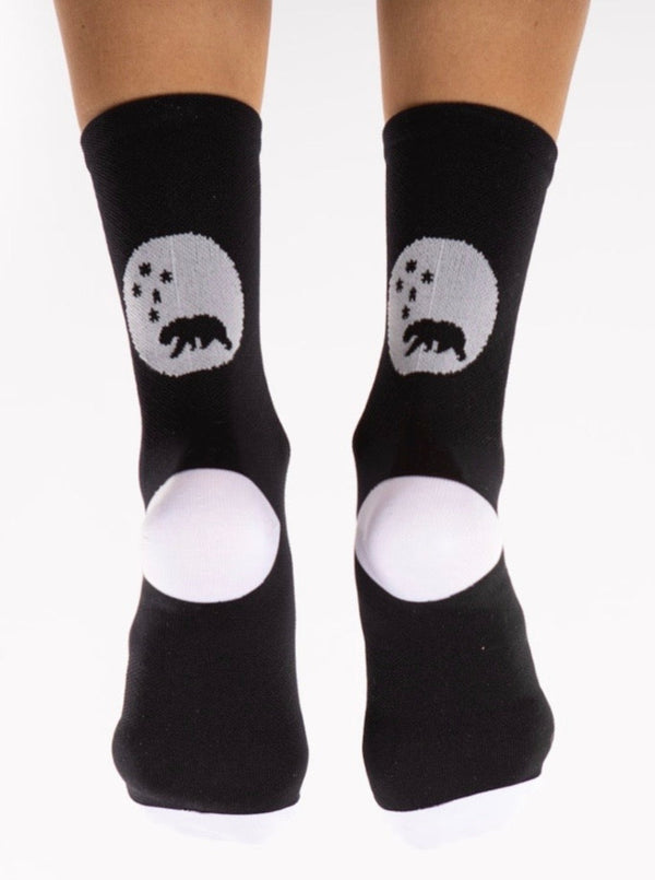 Back view of WYN republic Flagship Socks. Black cycling/running socks with white bear logo and heel.