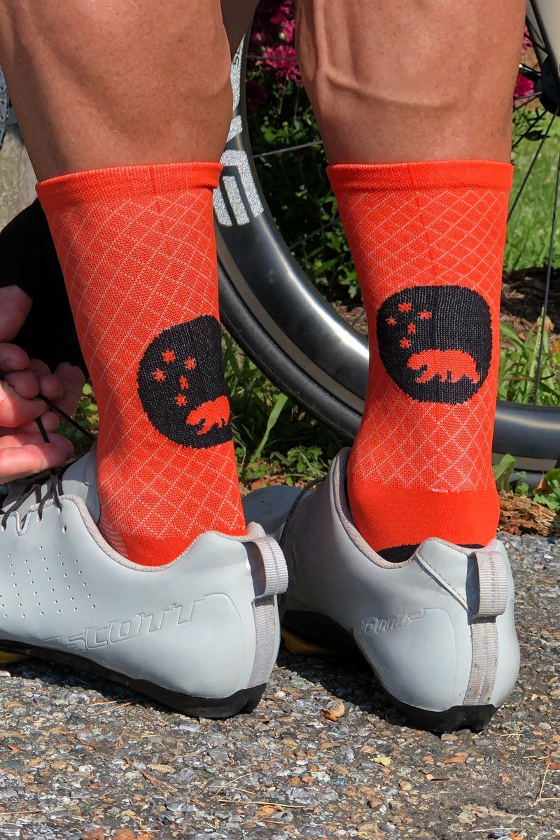 Back view Orange Flagship Socks in white cycling shoes. Mid-calf cycling socks with diamond weave.