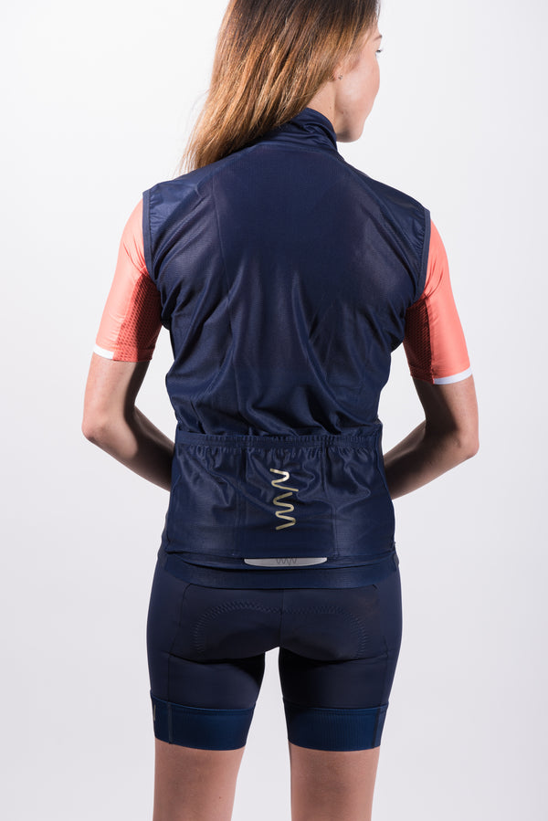 Back view women's gilet. Navy cycling vest with mesh panel and 3 storage pockets with reflective logo.