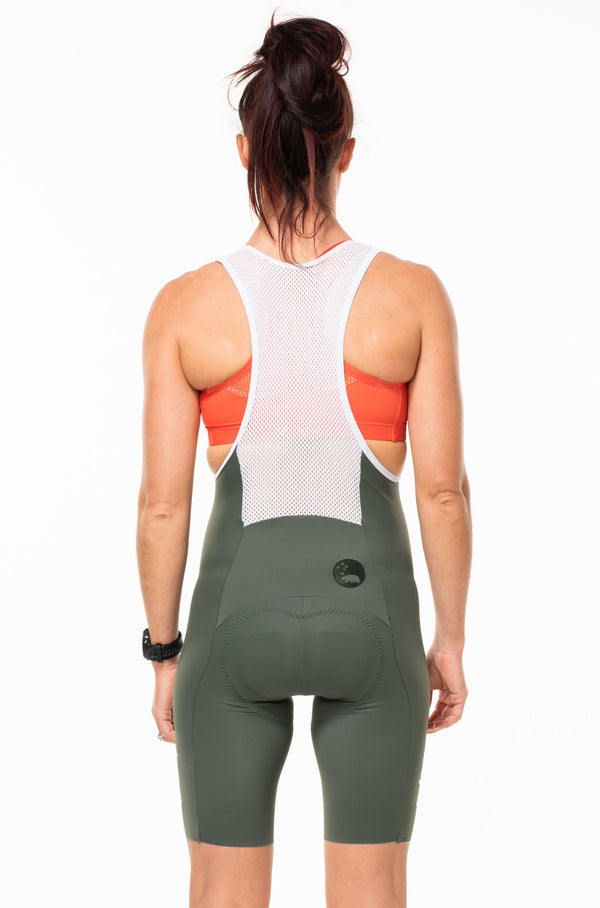 Back view of women's Velocity Cycling Bib Shorts. Aerodynamic cycling shorts. Green bib shorts with white mesh straps.