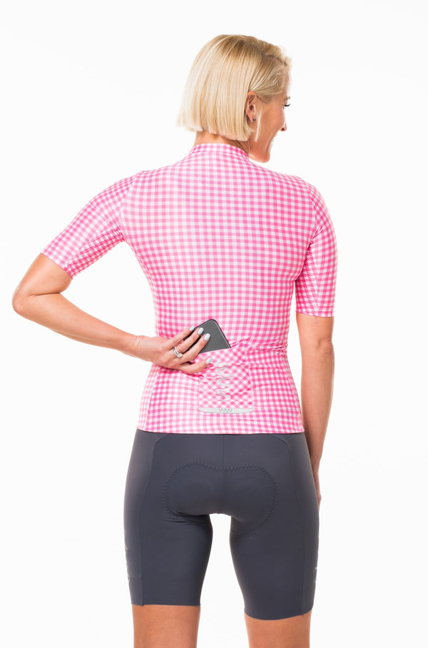 Model placing a phone in back pocket of gingham style cycling jersey. Fast women's cycling jersey with storage.