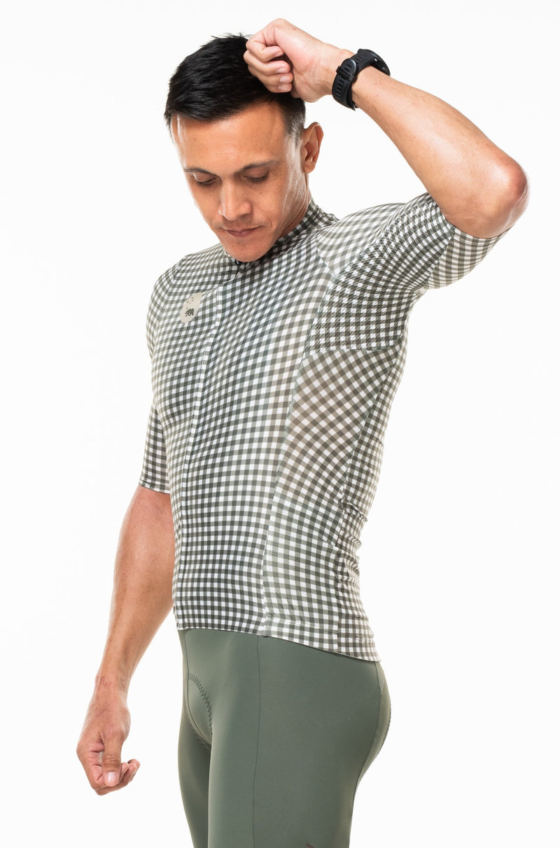 Model lifting left arm of Spruce cycling top. Green cycling jersey with ventilated sides.