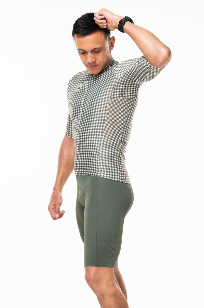 Model wearing men's Spruce bib shorts with matching cycling jersey. Green bib shorts with green checkered jersey.