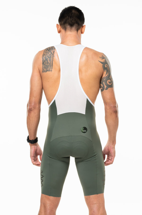 Back view of men's Velocity Cycling Bib Shorts. Aerodynamic green cycling shorts. Bib shorts with white mesh straps.