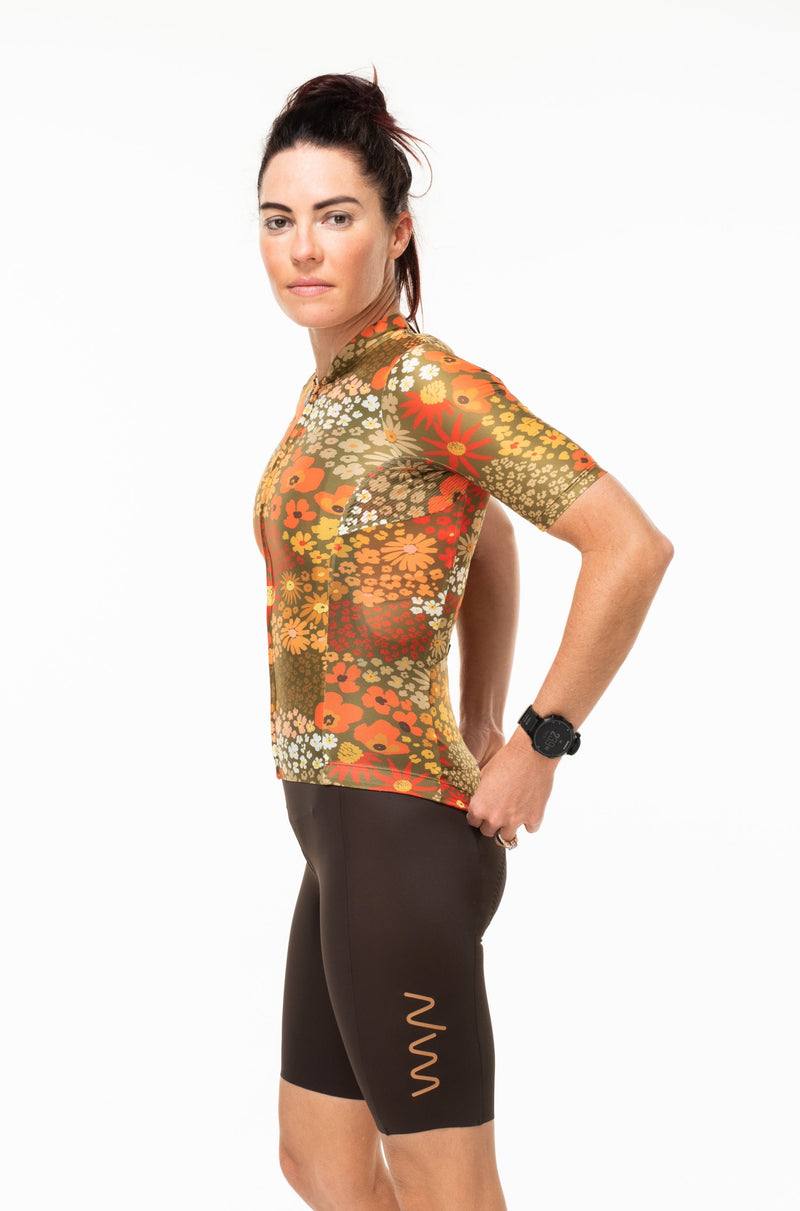Left view of Ochre cycling jersey. Women's orange cycling jersey with short sleeves.