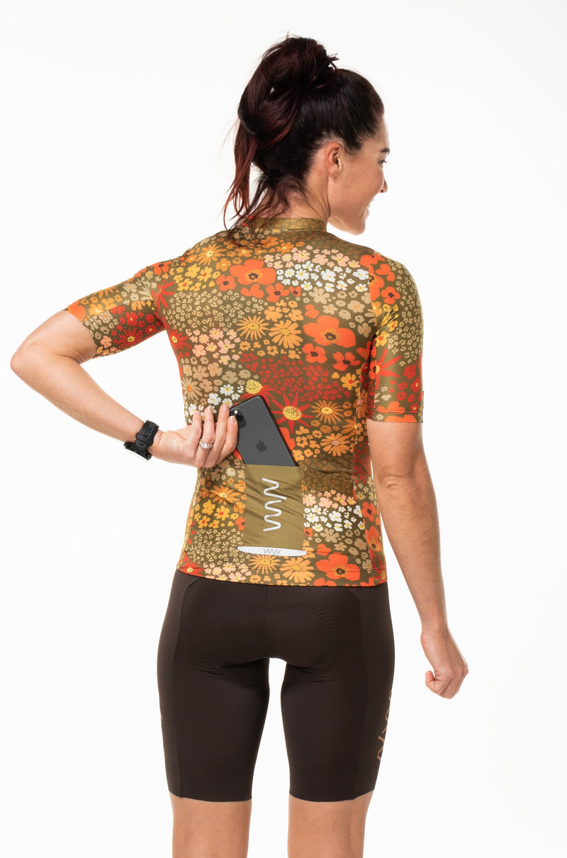 Model placing a phone in back pocket of Ochre cycling jersey. Retro women's cycling jersey with storage.
