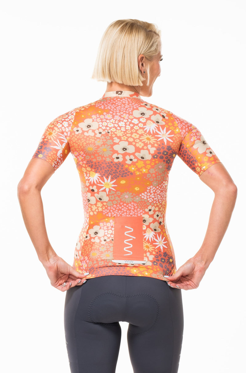 Model showing back view of Flower Child Blush Cycling Jersey. Pink flower print jersey with back storage and reflective logo.