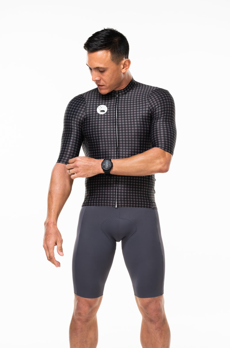 Model pulling sleeve of men's black and gray cycling jersey. Cycling jersey with sleeves that go to the elbow.