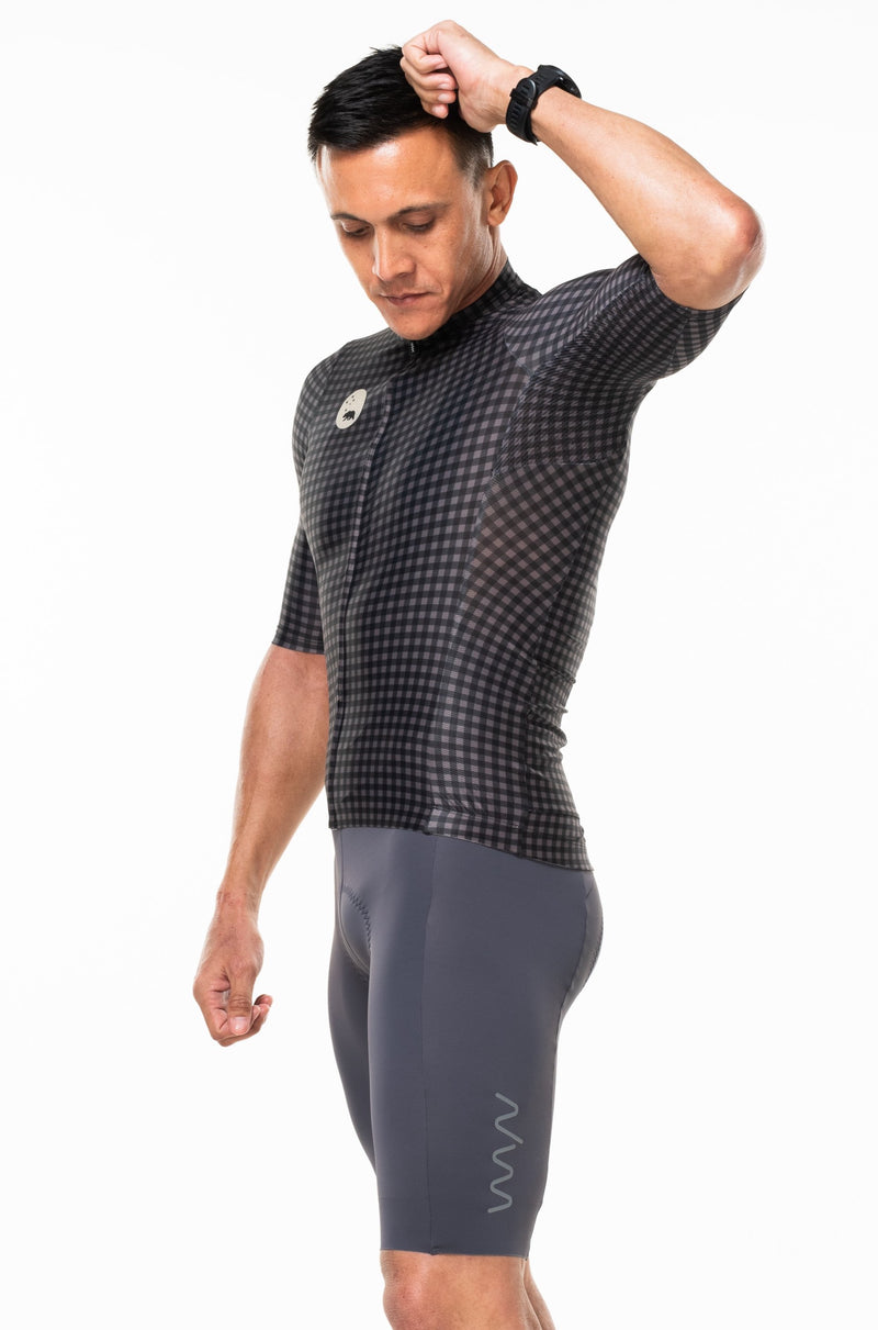 Model lifting left arm of Slate/Black cycling top. Cycling jersey with ventilated sides.