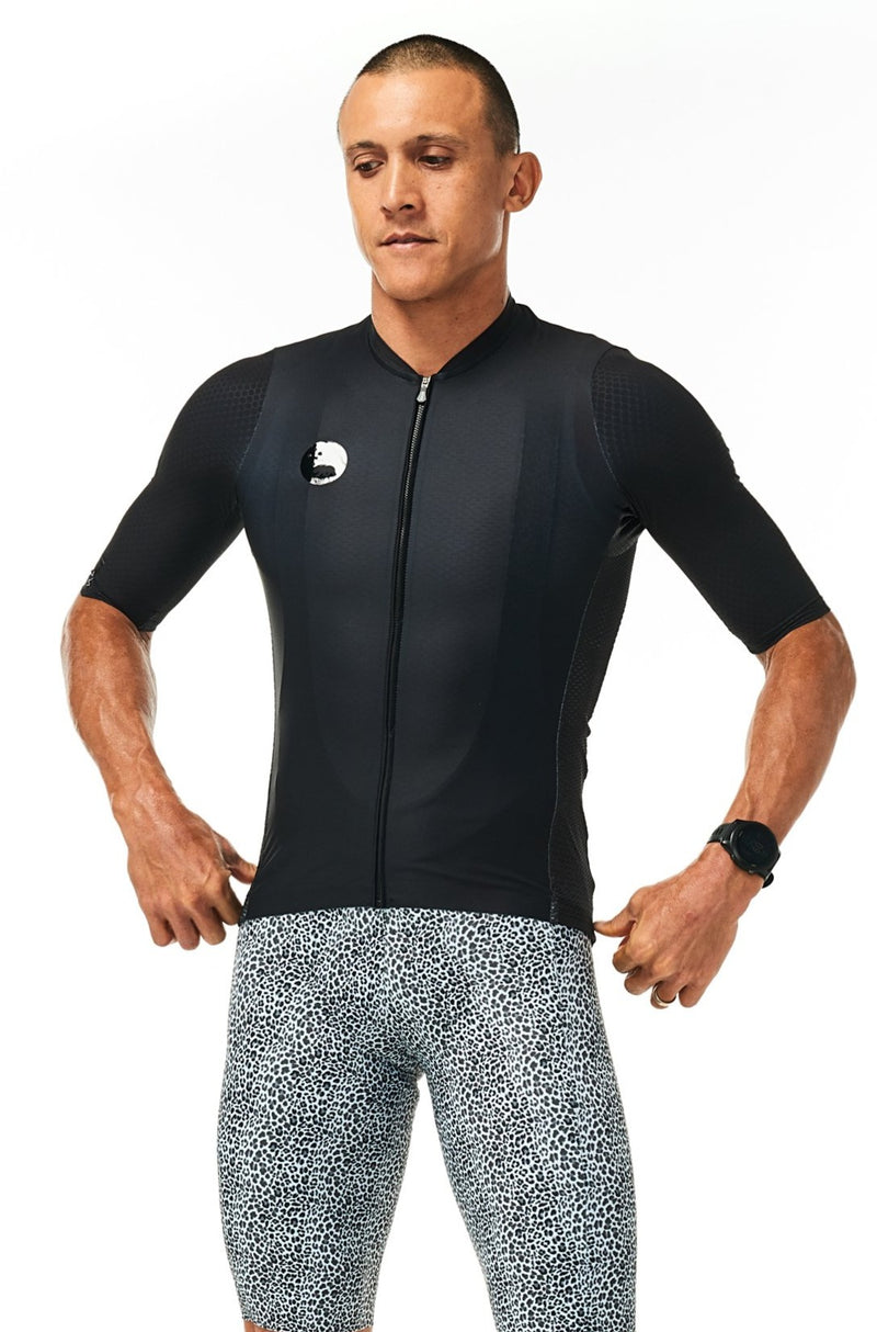 Model wearing men's Snow Leopard Velocity Cycling Bib Shorts with black jersey. Aero cycling shorts.