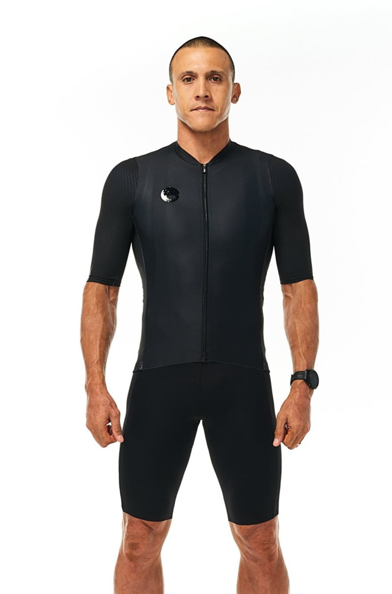 Model wearing men's black Velocity Cycling Bib Shorts with matching jersey. Aero cycling kit.