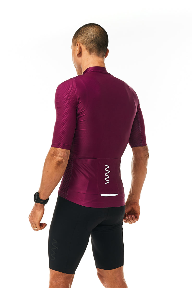 Back view model wearing men's black Velocity Cycling Bib Shorts with purple jersey. Performance cycling kit.