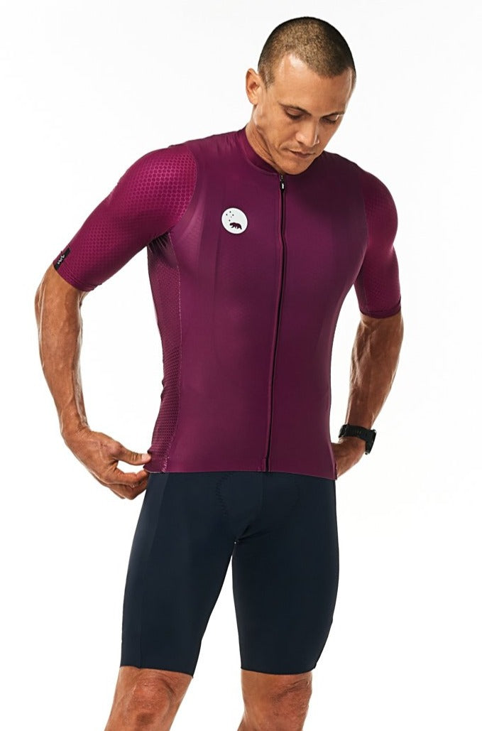 Model wearing men's navy Velocity Cycling Bib Shorts with purple jersey. Fast cycling kit.