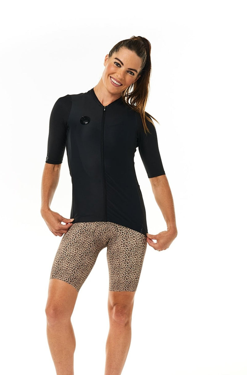 Model wearing women's Wild Cat Velocity Cycling Bib Shorts with black jersey. Leopard print shorts.