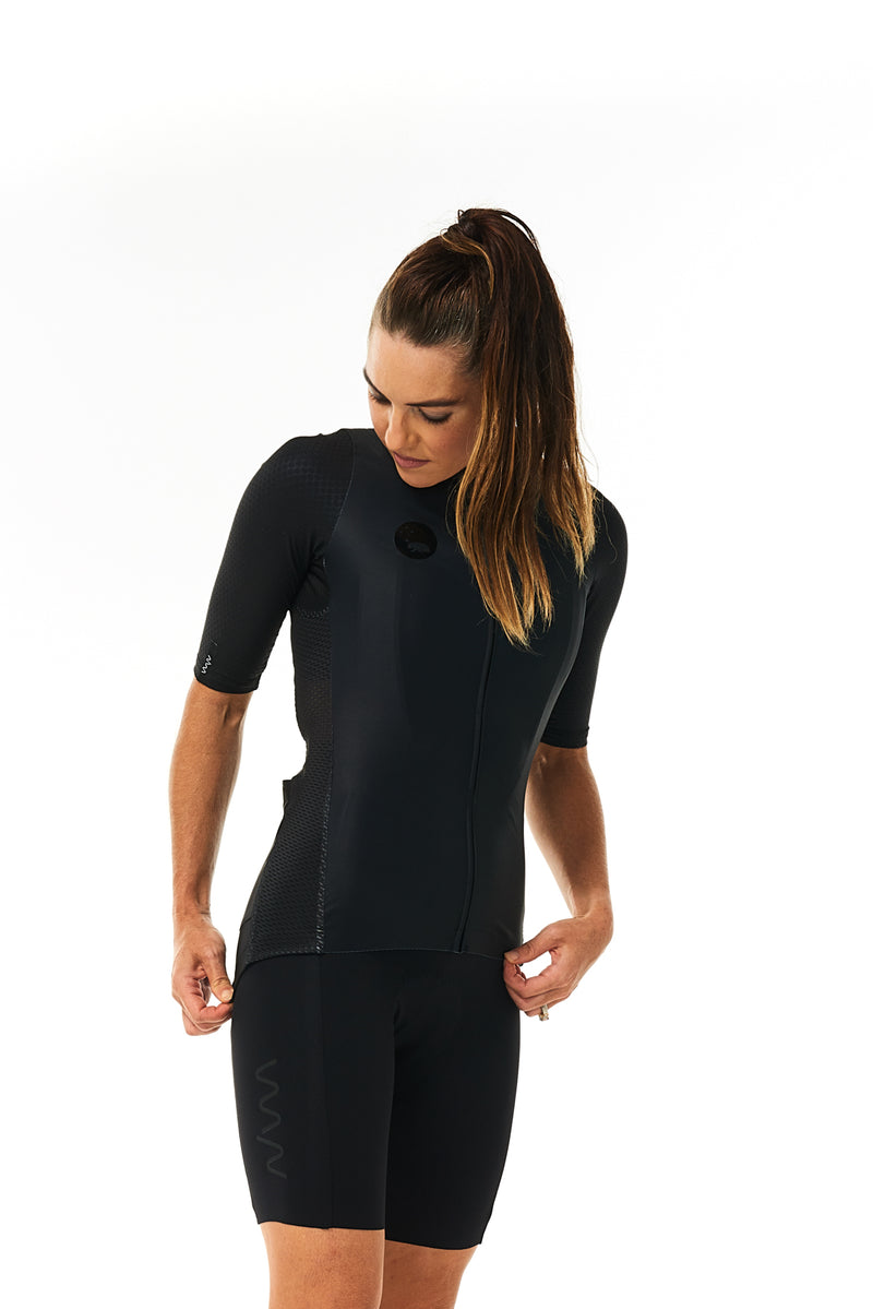 Model wearing women's black Velocity Cycling Bib Shorts with matching jersey. Aero cycling kit.