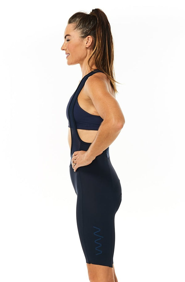 Left side of women's navy Velocity Cycling Bib Shorts. No-cuff aerodynamic cycling shorts.